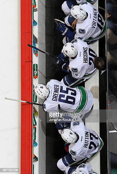 Jake Virtanen Chris Higgins Alexandre Grenier and Ben Hutton of the Vancouver Canucks look on from the bench during second period action against the...