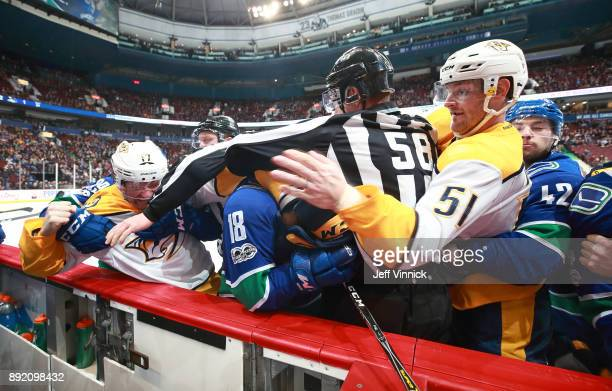 Jake Virtanen of the Vancouver Canucks and Austin Watson and Scott Hartnell of the Nashville Predators fight during their NHL game at Rogers Arena...