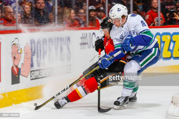 Jake Virtanen of the Vancouver Canucks and Brett Kulak of the Calgary Flames battle for the puck in a NHL game against the Vancouver Canucks at the...