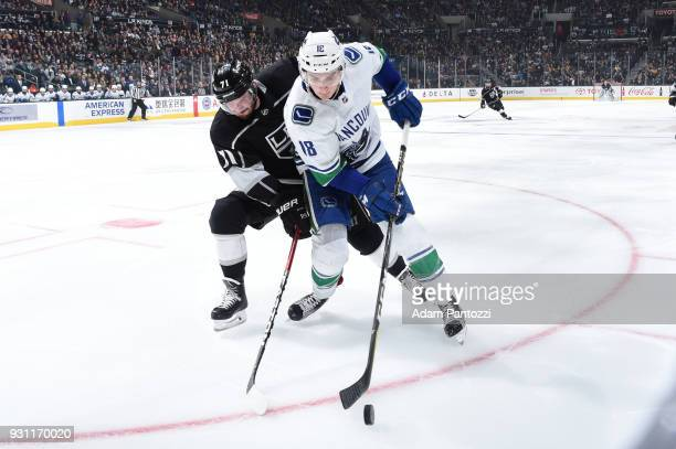 Jake Virtanen of the Vancouver Canucks battles for the puck against Torrey Mitchell of the Los Angeles Kings at STAPLES Center on March 12 2018 in...