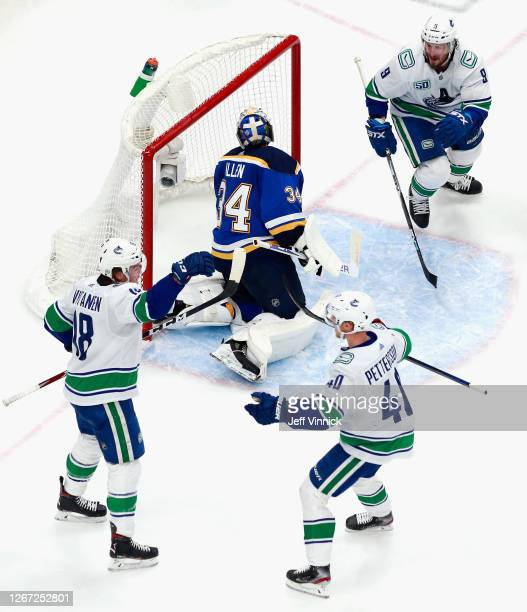Jake Virtanen of the Vancouver Canucks celebrates his goal at 16:08 of the second period against Jake Allen of the St. Louis Blues and is joined by...