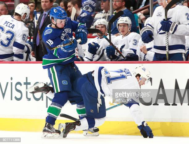 Jake Virtanen of the Vancouver Canucks checks Brayden Point of the Tampa Bay Lightning during their NHL game at Rogers Arena February 3 2018 in...