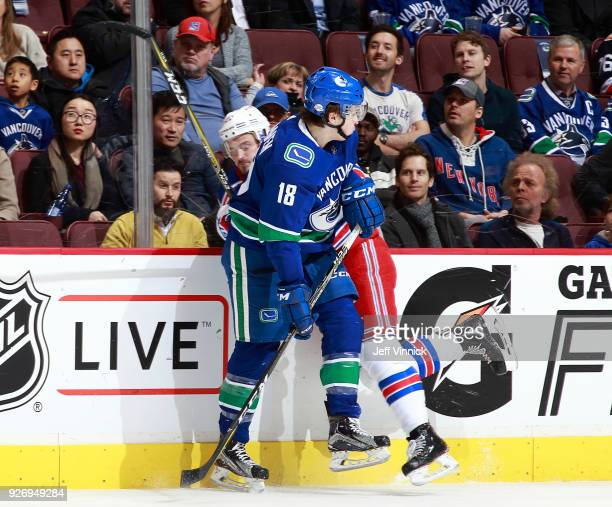 Jake Virtanen of the Vancouver Canucks checks Chris Kreider of the New York Rangers during their NHL game at Rogers Arena February 28 2018 in...