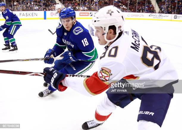 Jake Virtanen of the Vancouver Canucks checks Jared McCann of the Florida Panthers during their NHL game at Rogers Arena February 14 2018 in...