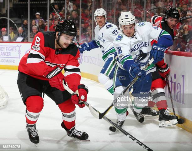 Jake Virtanen of the Vancouver Canucks checks Stefan Noesen of the New Jersey Devils during the first period on November 24 2017 at the Prudential...