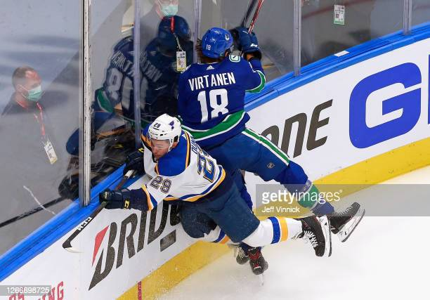 Jake Virtanen of the Vancouver Canucks checks Vince Dunn of the St. Louis Blues during the first period in Game Four of the Western Conference First...