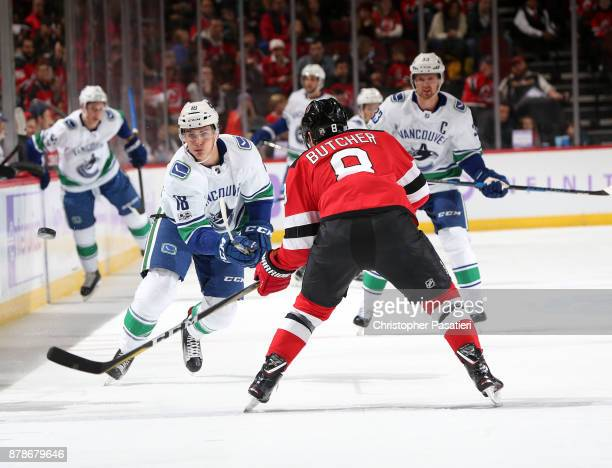 Jake Virtanen of the Vancouver Canucks clears the puck into the zone against Will Butcher of the New Jersey Devils during the first period on...