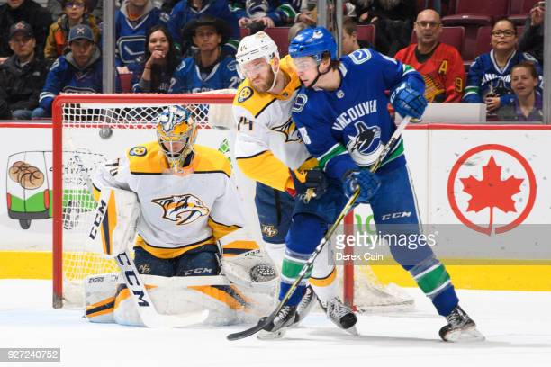 Jake Virtanen of the Vancouver Canucks deflects the puck past Mattias Ekholm and Juuse Saros of the Nashville Predators during their NHL game at...
