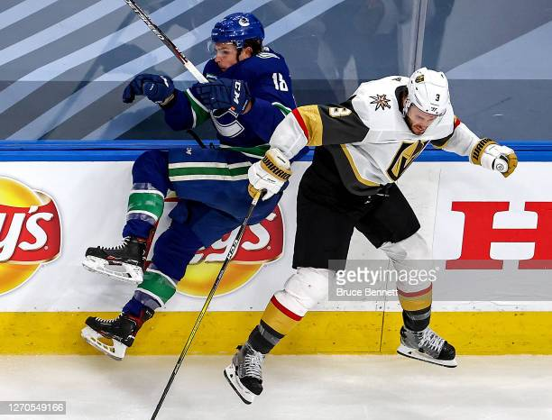 Jake Virtanen of the Vancouver Canucks is checked by Brayden McNabb of the Vegas Golden Knights during the third period in Game Six of the Western...
