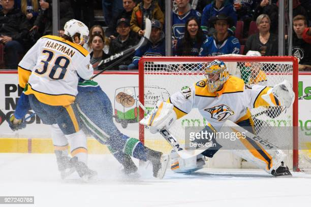 Jake Virtanen of the Vancouver Canucks is checked by Ryan Hartman as Juuse Saros of the Nashville Predators tracks the puck during their NHL game at...