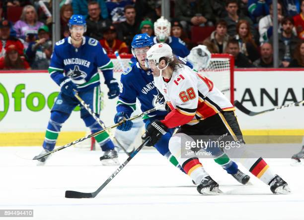 Jake Virtanen of the Vancouver Canucks looks on as Jaromir Jagr of the Calgary Flames skates up ice with the puck during their NHL game at Rogers...