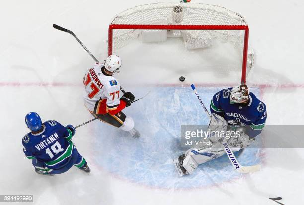 Jake Virtanen of the Vancouver Canucks looks on as Mark Jankowski of the Calgary Flames scores on Jacob Markstrom of the Vancouver Canucks during...