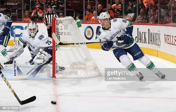 Jake Virtanen of the Vancouver Canucks passes the puck alongside goaltender Jacob Markstrom against the Philadelphia Flyers on November 21 2017 at...