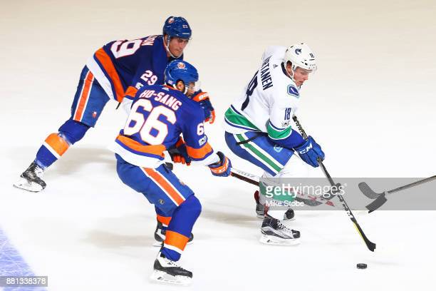 Jake Virtanen of the Vancouver Canucks plays the puck against Joshua HoSang and Brock Nelson of the New York Islanders at Barclays Center on November...