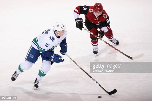 Jake Virtanen of the Vancouver Canucks skates the puck past Clayton Keller of the Arizona Coyotes during the second period of the NHL game at Gila...
