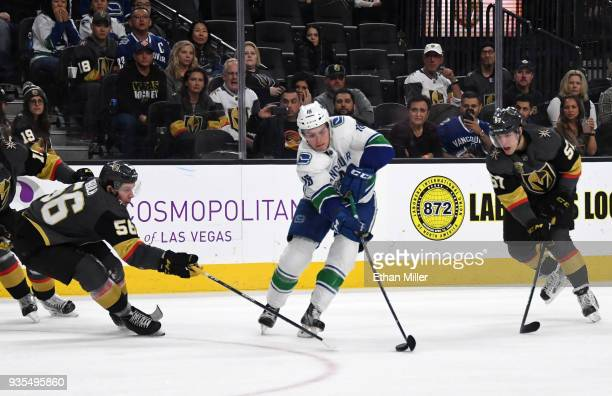 Jake Virtanen of the Vancouver Canucks skates with the puck between Erik Haula and David Perron of the Vegas Golden Knights in the third period of...