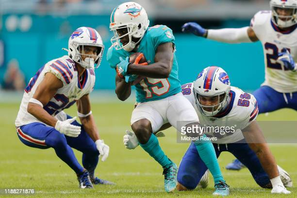 Jakeem Grant of the Miami Dolphins is tackled by Matt Milano and Micah Hyde of the Buffalo Bills during the fourth quarter at Hard Rock Stadium on...