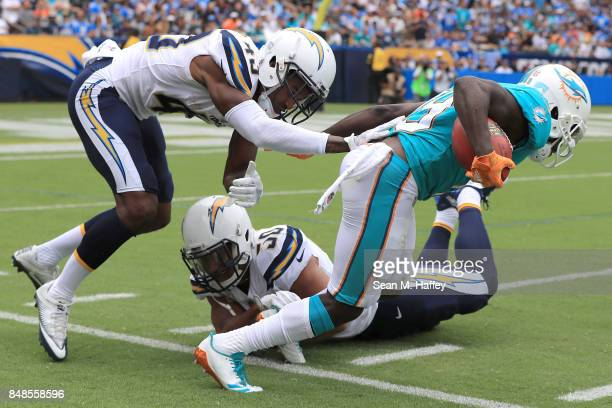 Jakeem Grant of the Miami Dolphins returns the punt and tries to get around Michael Davis of the Los Angeles Chargers and Charmeachealle Moore of the...