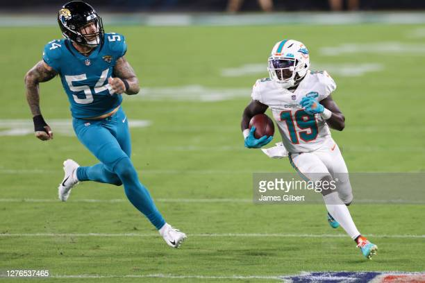 Jakeem Grant of the Miami Dolphins runs for yardage against Cassius Marsh of the Jacksonville Jaguars during the first quarter of a game at TIAA Bank...