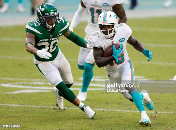 Jakeem Grant of the Miami Dolphins runs with the ball after breaking a tackle by Bradley McDougald of the New York Jets during the first half of...