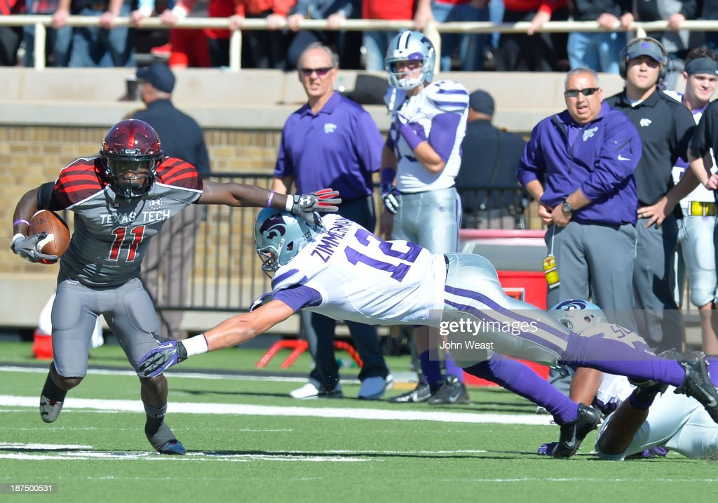 Jakeem Grant #11 of the Texas Tech Red Raiders avoids a tackle by Ty Zimmerman #12 of the Kansas State Wildcats during game action on November 9, 2013 at AT&T Jones Stadium in Lubbock, Texas. The Kansas State Wildcats won the game 49-26.