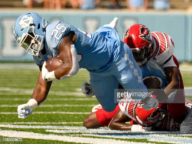Jakeen Harris and Shyheim Battle of the North Carolina State Wolfpack tackle Javonte Williams of the North Carolina Tar Heelsduring their game at...