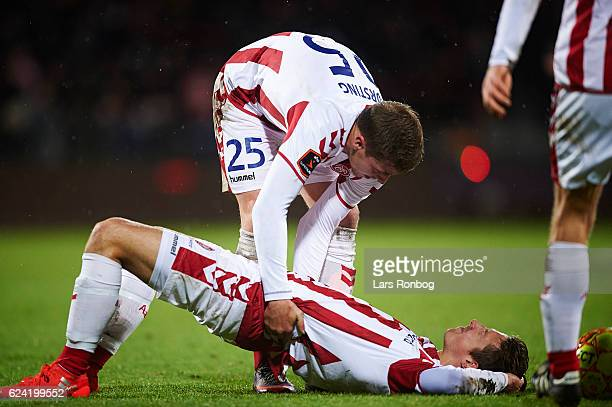 Jakob Ahlmann of AaB Aalborg lies injured on the pitch and helped by Frederik Borsting of AaB Aalborg during the Danish Alka Superliga match between...