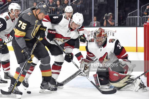 Jakob Chychrun and Antti Raanta of the Arizona Coyotes defend their goal against Ryan Reaves of the Vegas Golden Knights during the game at TMobile...