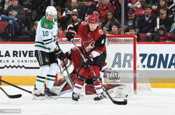 Jakob Chychrun of the Arizona Coyotes attempts to block a shot on goal as Corey Perry of the Dallas Stars sets up in front of the net for a scoring...