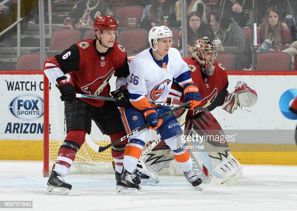 Jakob Chychrun of the Arizona Coyotes battles for position with Tanner Fritz of the New York Islanders in front of Coyotes goaltender Antti Raanta at...