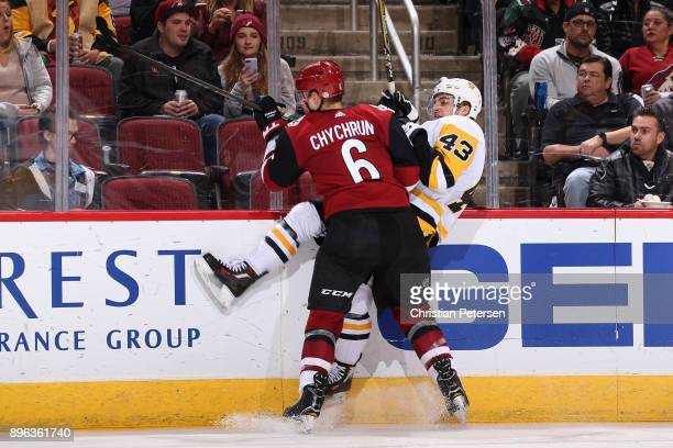 Jakob Chychrun of the Arizona Coyotes checks Conor Sheary of the Pittsburgh Penguins during the second period of the NHL game at Gila River Arena on...
