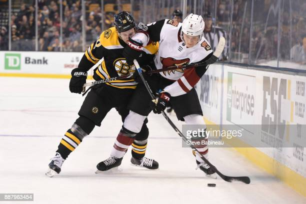 Jakob Chychrun of the Arizona Coyotes fights for the puck against Anders Bjork of the Boston Bruins at the TD Garden on December 7 2017 in Boston...