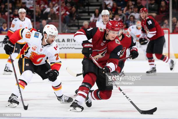 Jakob Chychrun of the Arizona Coyotes skates with the puck ahead of Dillon Dube of the Calgary Flames during the third period of the NHL game at Gila...