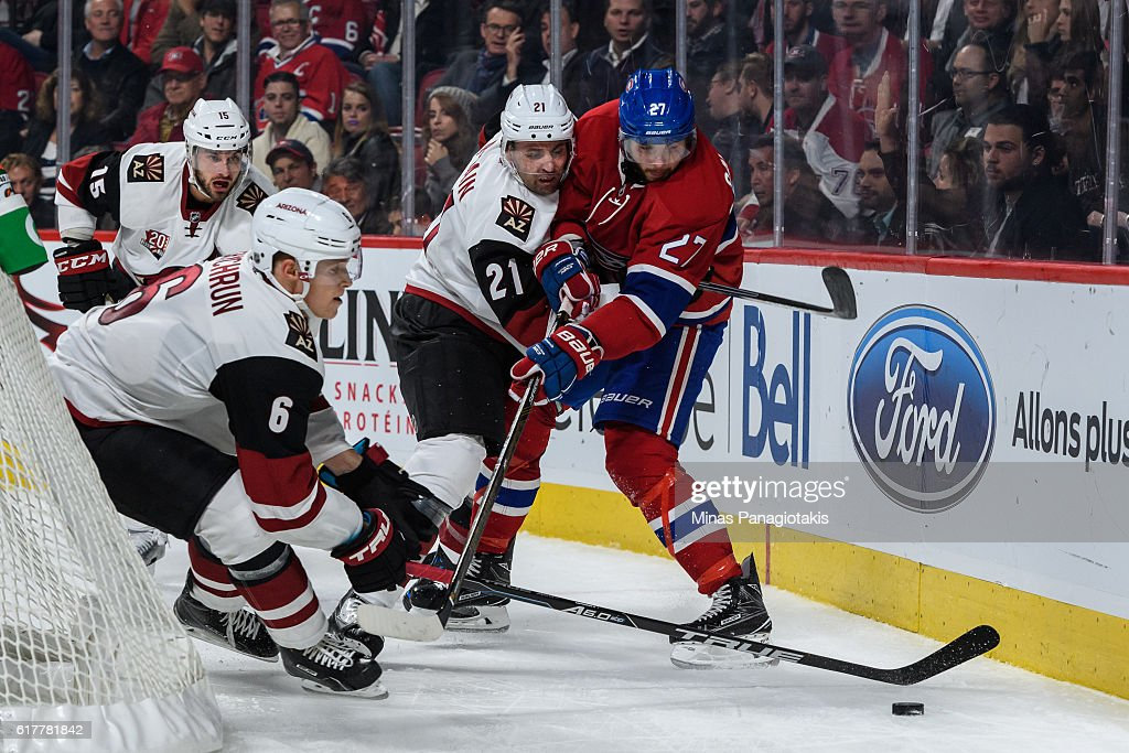Jakob Chychrun #6 of the Arizona Coyotes tries to get possession of the puck while teammate Jamie McBain #21 defends against Alex Galchenyuk #27 of the Montreal Canadiens during the NHL game at the Bell Centre on October 20, 2016 in Montreal, Quebec, Canada. The Montreal Canadiens defeated the Arizona Coyotes 5-2.