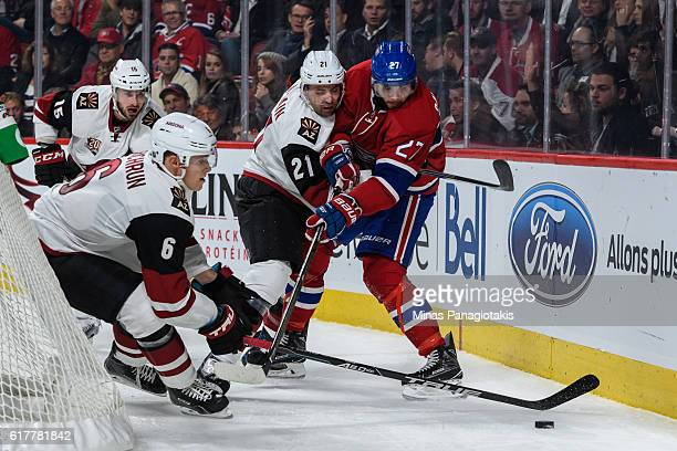 Jakob Chychrun of the Arizona Coyotes tries to get possession of the puck while teammate Jamie McBain defends against Alex Galchenyuk of the Montreal...
