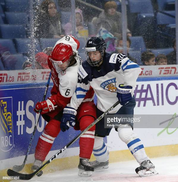 Jakob Jessen of Denmark and Rasmus Kupari of Finland go after a puck in the corner in the second period during the IIHF World Junior Championship at...