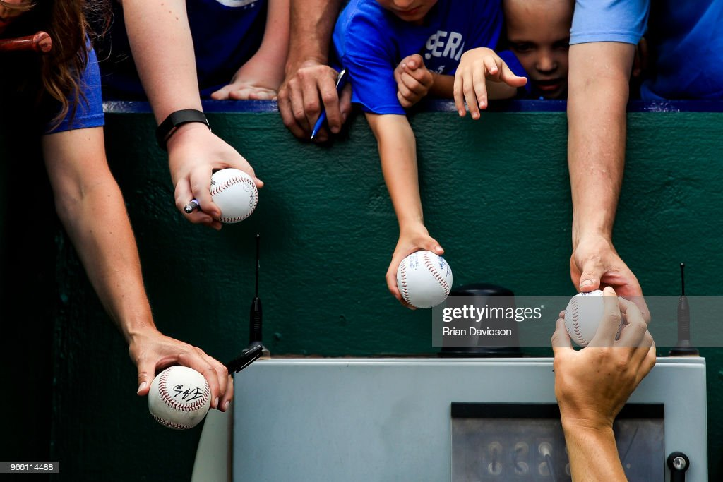 Jakob Junis #65 of the Kansas City Royals signs autographs for fans before the game against the Oakland Athletics at Kauffman Stadium on June 2, 2018 in Kansas City, Missouri.