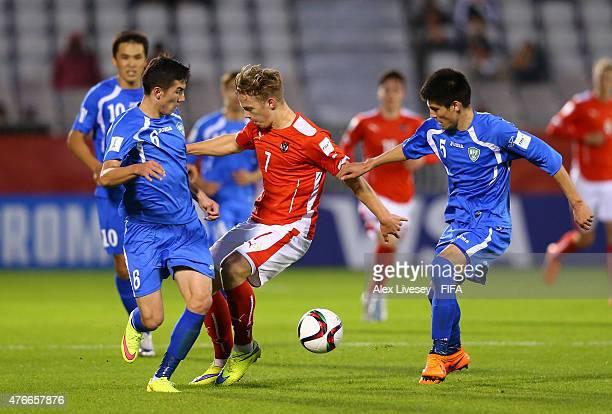 Jakob Kreuzer of Austria is stopped by Akramjon Komilov and Odiljon Hamrobekov of Uzbekistan during the FIFA U20 World Cup round of 16 match between...