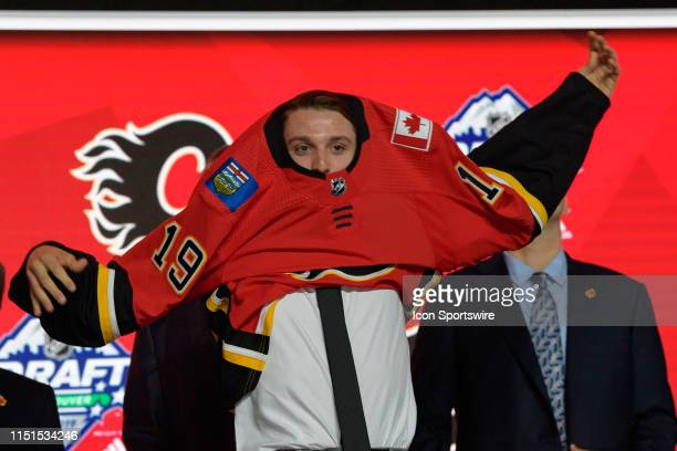 Jakob Pelletier puts on a jersey after being picked twenty-six overall by the Calgary Flames during the first round of the 2019 NHL Draft at Rogers...