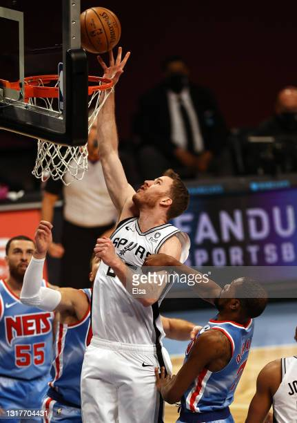 Jakob Poeltl of the San Antonio Spurs heads for the net as Kevin Durant of the Brooklyn Nets defends in the first quarter at Barclays Center on May...