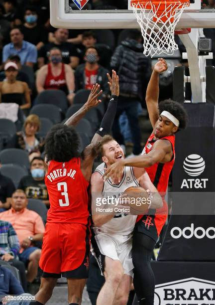 Jakob Poeltl of the San Antonio Spurs is fouled by Mason Jones of the Houston Rockets as teammate Kevin Porter of the Houston Rockets is on the left...