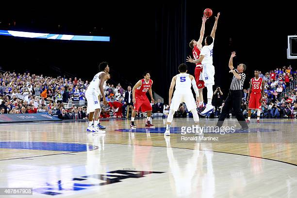 Jakob Poeltl of the Utah Utes and Jahlil Okafor of the Duke Blue Devils take the opening jump ball during a South Regional Semifinal game of the 2015...
