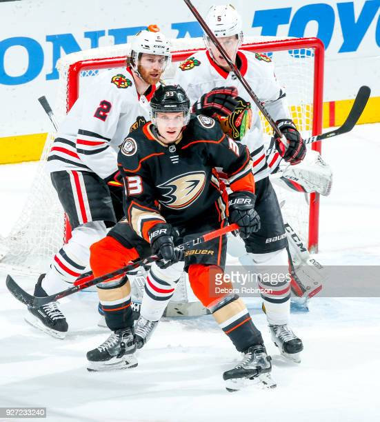 Jakob Silfverberg of the Anaheim Ducks battles for position with Duncan Keith and Connor Murphy of the Chicago Blackhawks during the second period of...