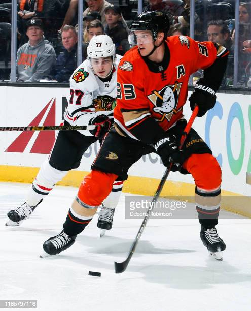 Jakob Silfverberg of the Anaheim Ducks skates with the puck with pressure from Kirby Dach of the Chicago Blackhawks during the third period of the...