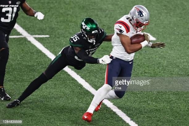 Jakobi Meyers of the New England Patriots carries the ball as Pierre Desir of the New York Jets defends during the first half at MetLife Stadium on...