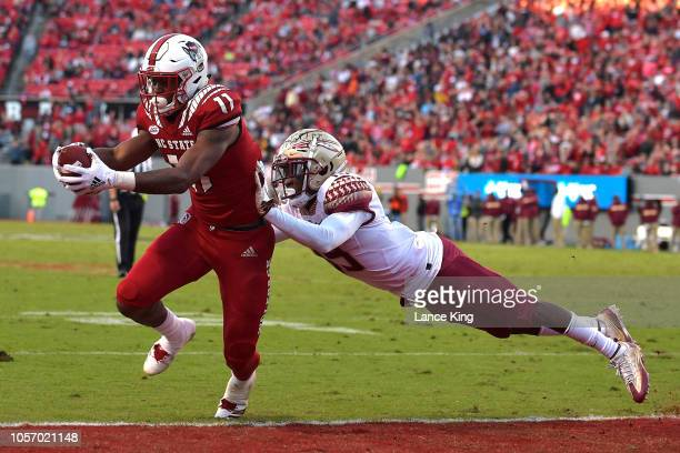 Jakobi Meyers of the North Carolina State Wolfpack catches a pass for a twoyard touchdown against AJ Westbrook of the Florida State Seminoles at...
