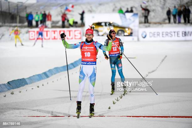 Jakov Fak of Slovenia crosses the finish line to finish second ahead of Quentin Fillon Maillet of France at the end of the men's 125 km pursuit event...