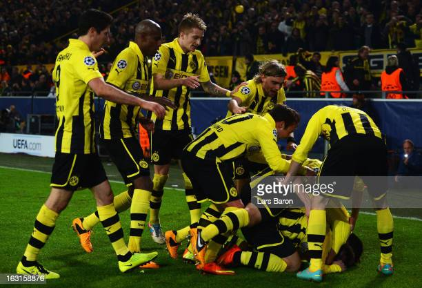 Jakub Blaszczykowski of Dortmund celebrates with team mates after scoring his teams third goal during the UEFA Champions League round of 16 second...