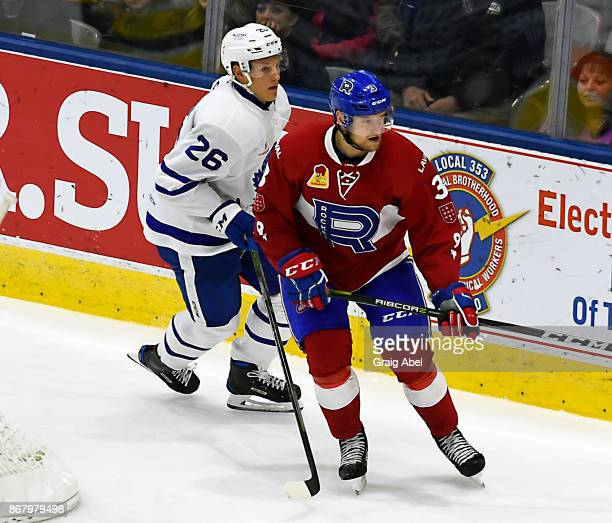 Jakub Jerabek of the Laval Rocket battles with Nikita Soshnikov of the Toronto Marlies during AHL game action on October 28 2017 at Ricoh Coliseum in...