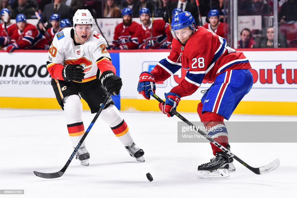 Jakub Jerabek #28 of the Montreal Canadien skates the puck against Curtis Lazar #20 of the Calgary Flames during the NHL game at the Bell Centre on December 7, 2017 in Montreal, Quebec, Canada. The Calgary Flames defeated the Montreal Canadiens 3-2 in overtime.